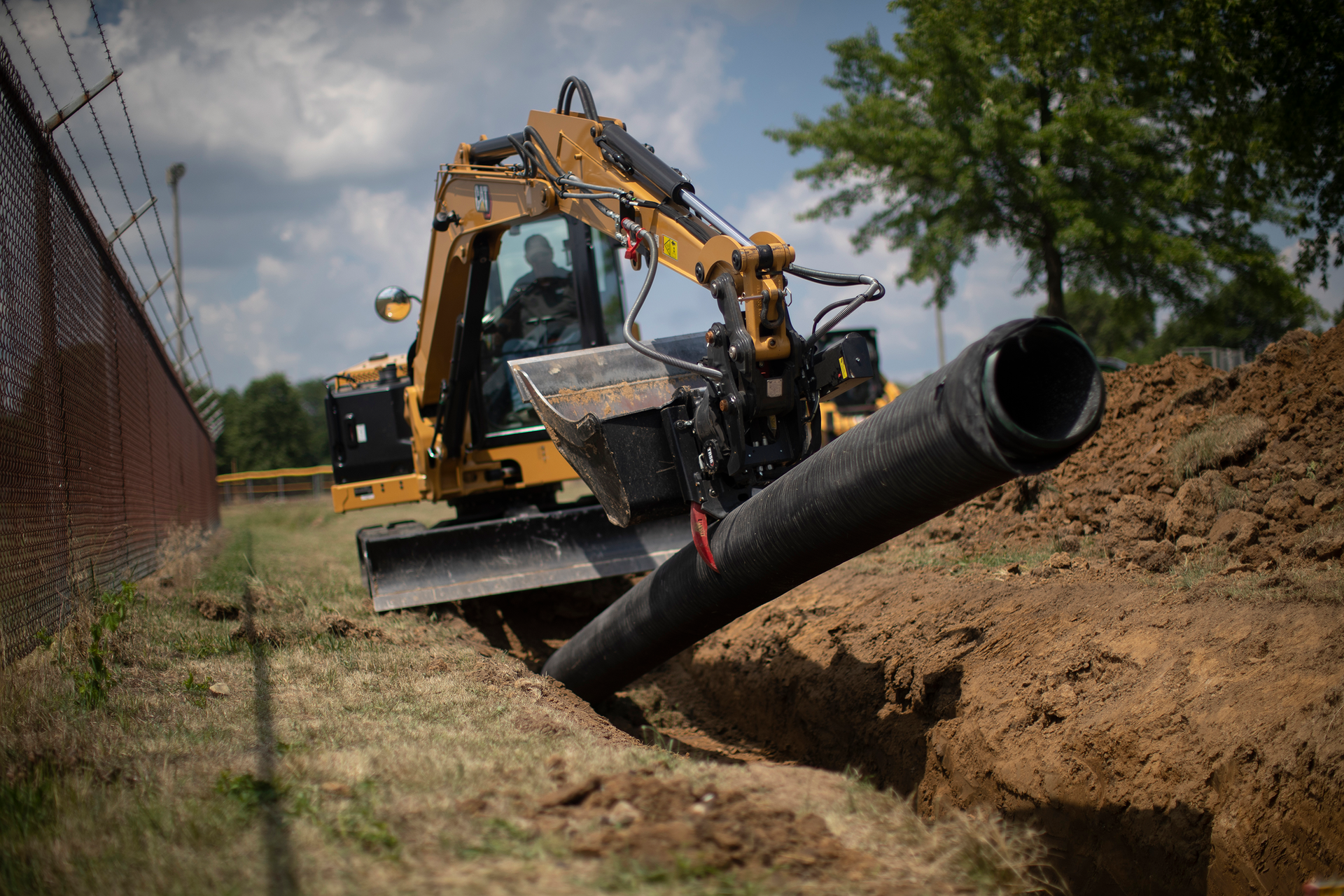 Cat 306CR compact excavator laying pipe